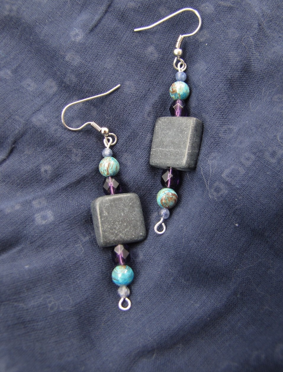central square of blackstone, with symmetrical beads on either side: faceted purple glass dodecahedron, swirly blue-and-brown 6mm jasper bead, tiny iolite bead