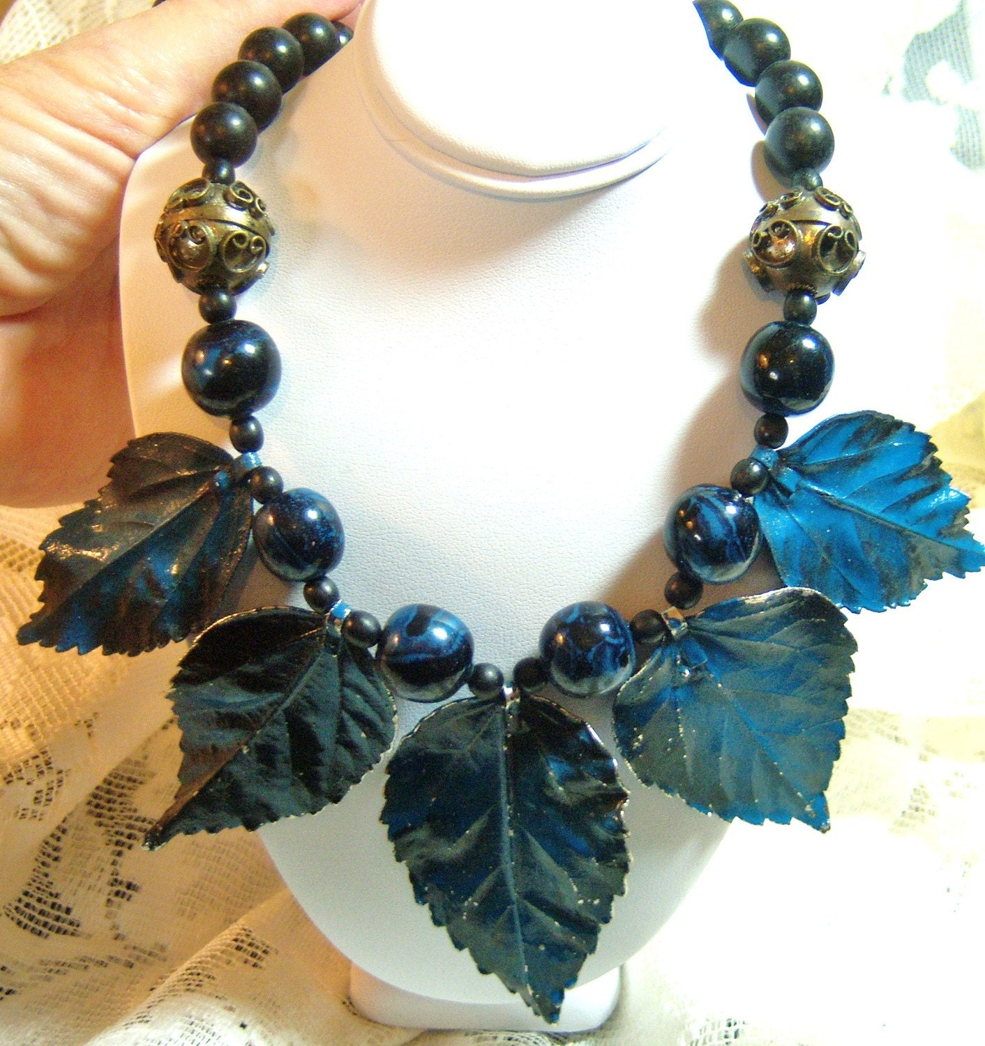 iridescent vintage necklace with black beads and blue leaves
