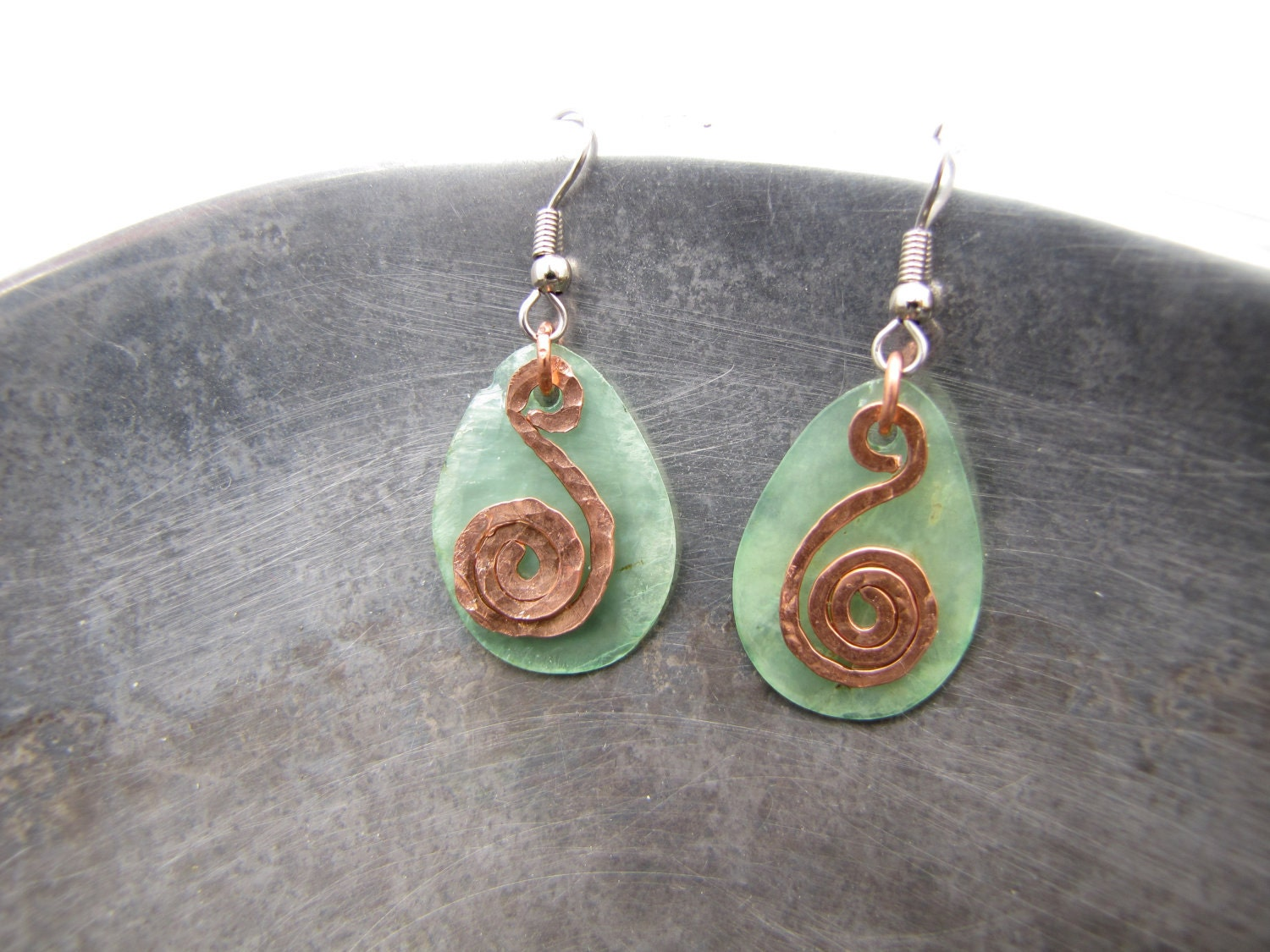 earrings: pale mint green capiz shell teardrops with flat-hammered-copper wire shaped into a spiral placed in front, looking somewhat like a treble clef