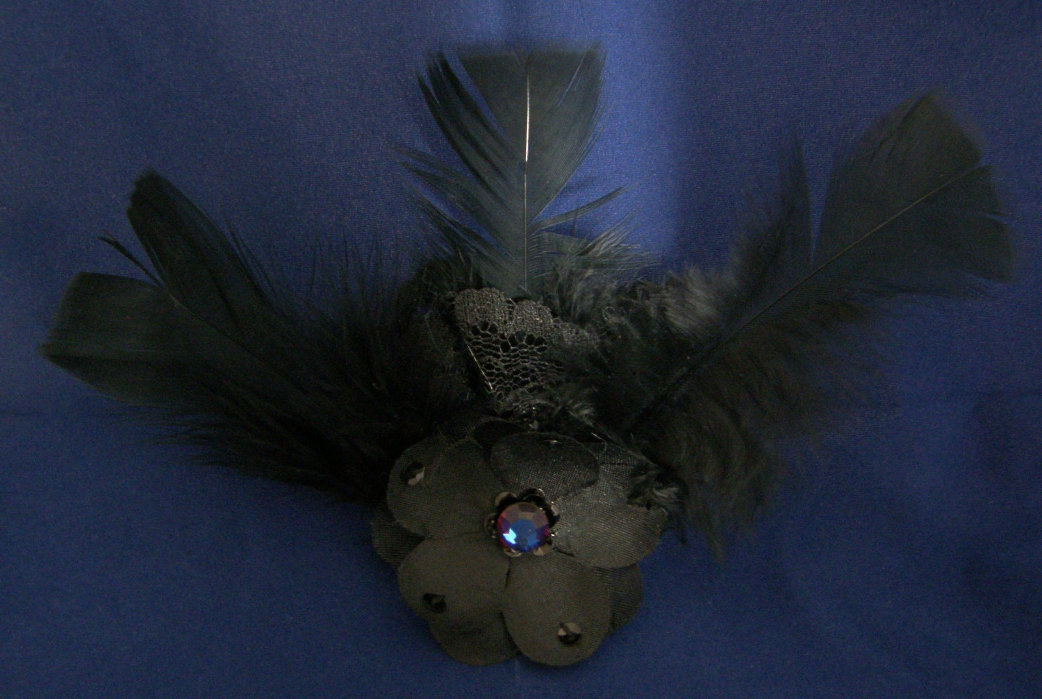 black floral barrette with feathers, lace, and iridescent stone